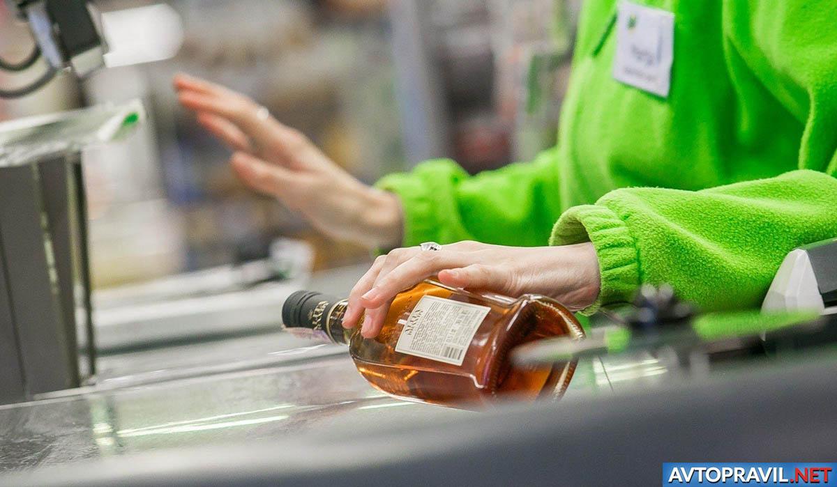 Касир с бутылкой алкоголя