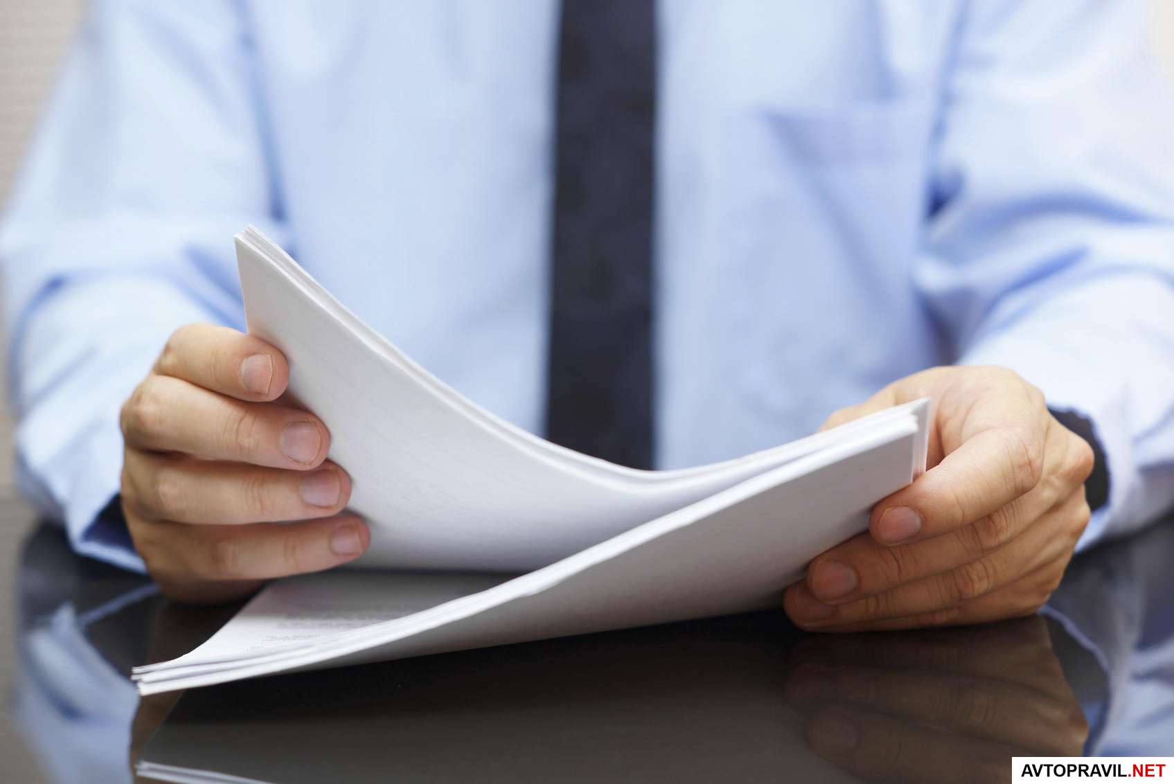 документы  в руках у человека, сидящего за столом