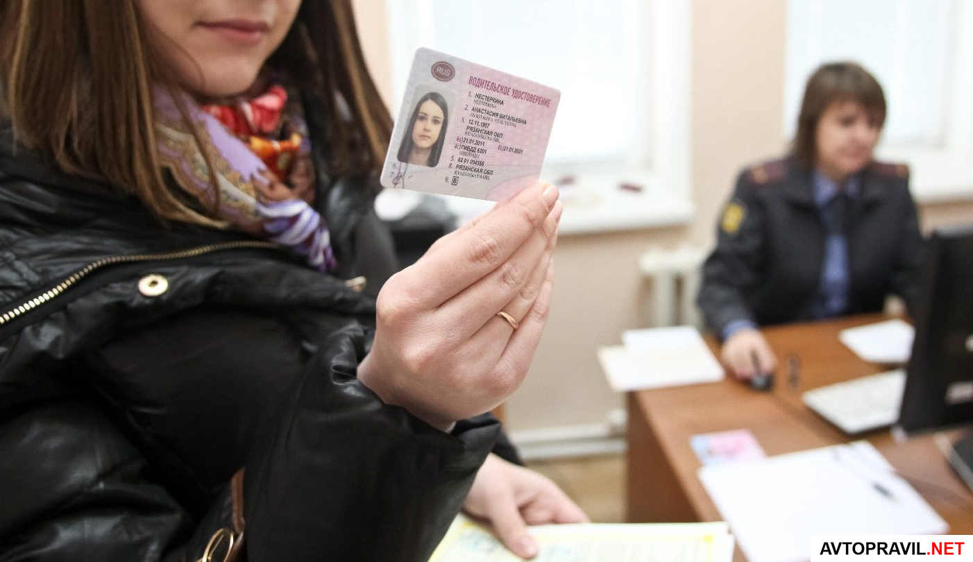 Водительское удостоверение в руках женщины, которая находится в участке ГИБДД