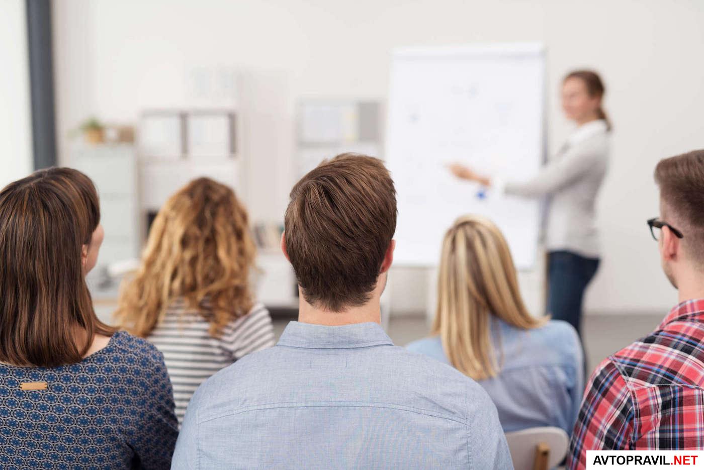Аудитория студентов и преподаватель на заднем плане