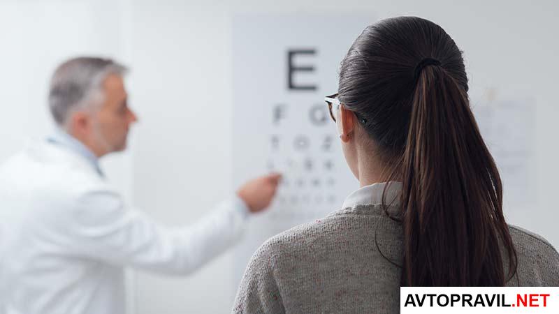 Окулист, проверяющий зрение женщины