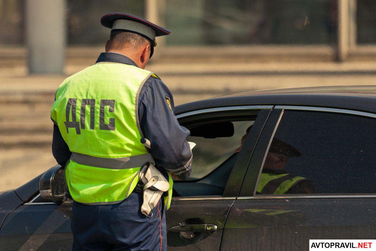 Сотрудник полиции стоящий возле машины