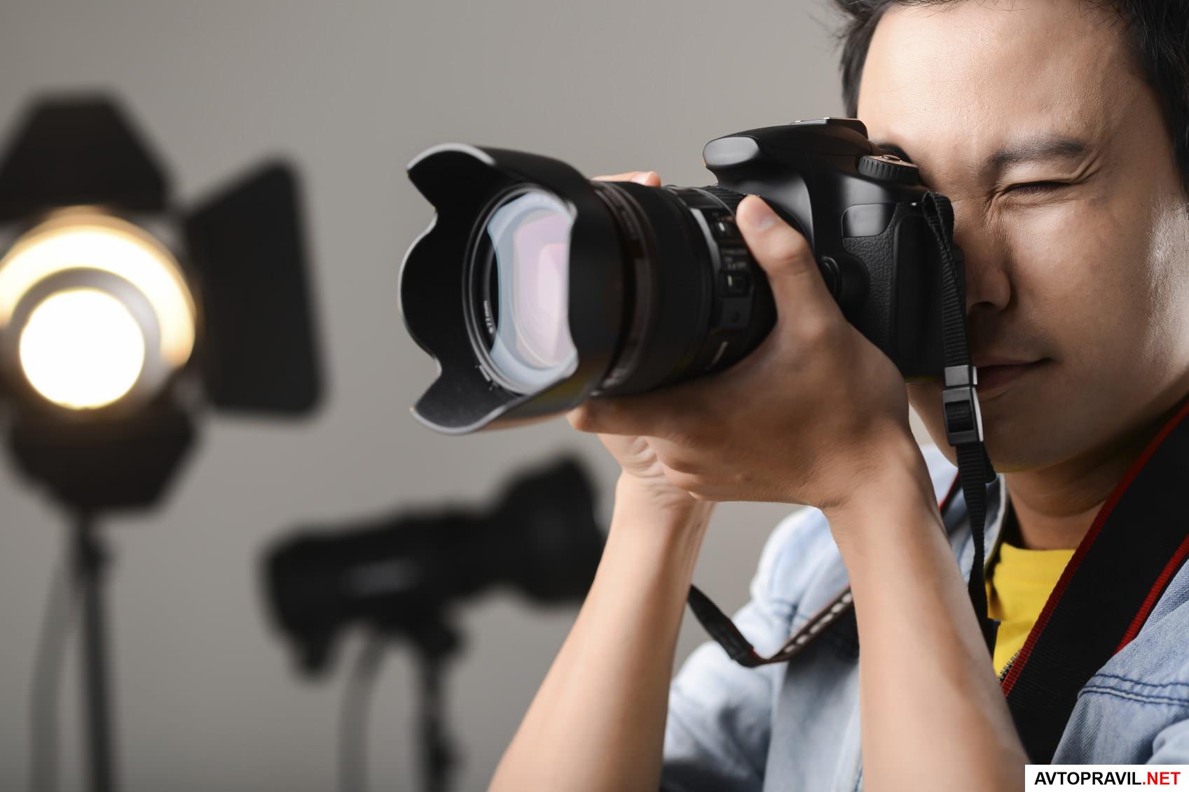 Фотограф, держащий фотоаппарат в руках