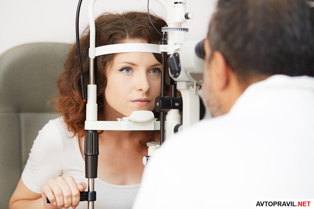 Окулист, проверяющий зрение на специальном аппарате
