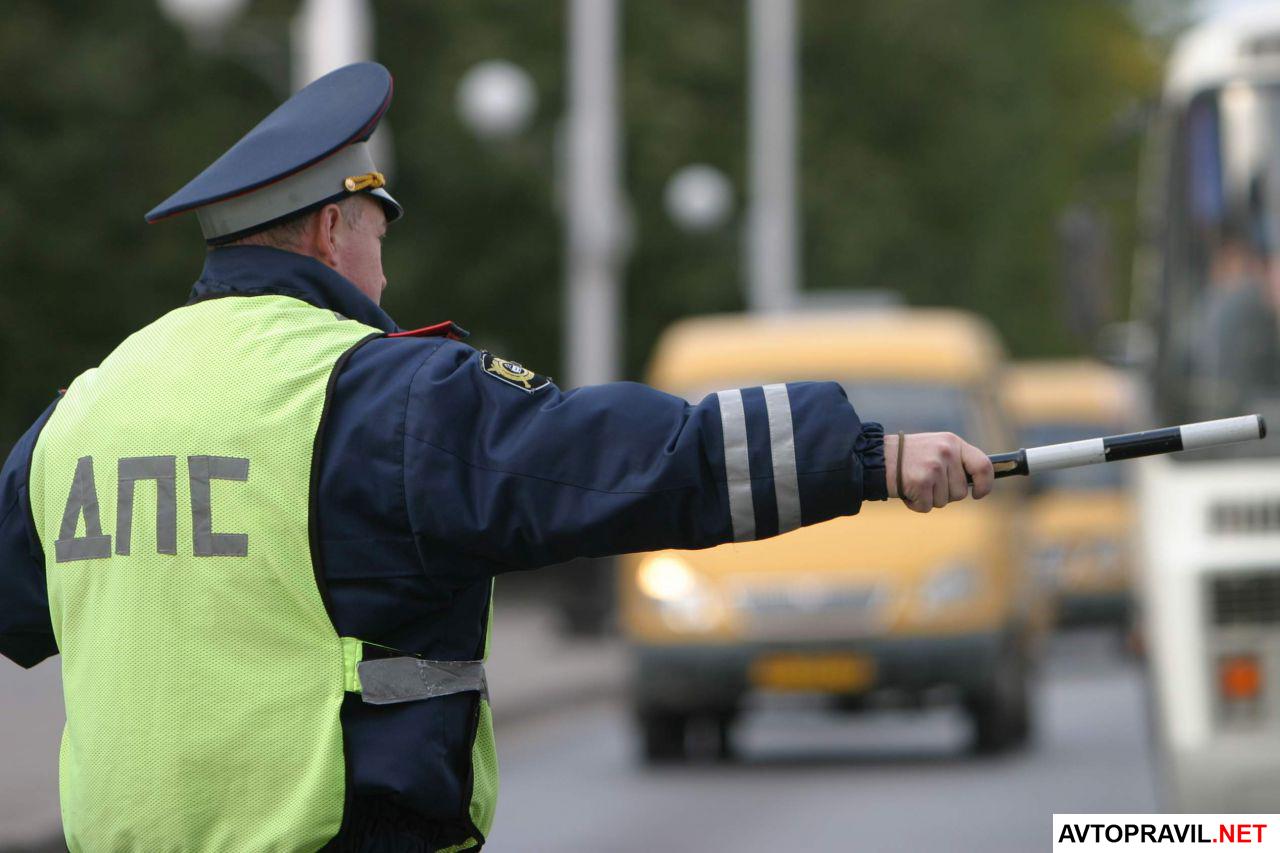 сотрудник полиции останавливает машину