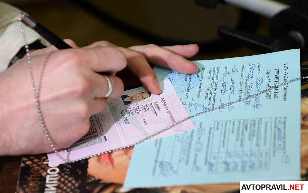 Женские руки с ручкой и водительскими правами