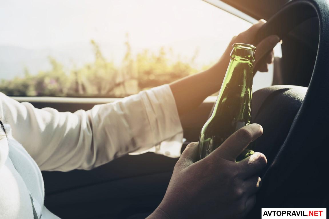 Человек держащий бутылку пива за рулем авто