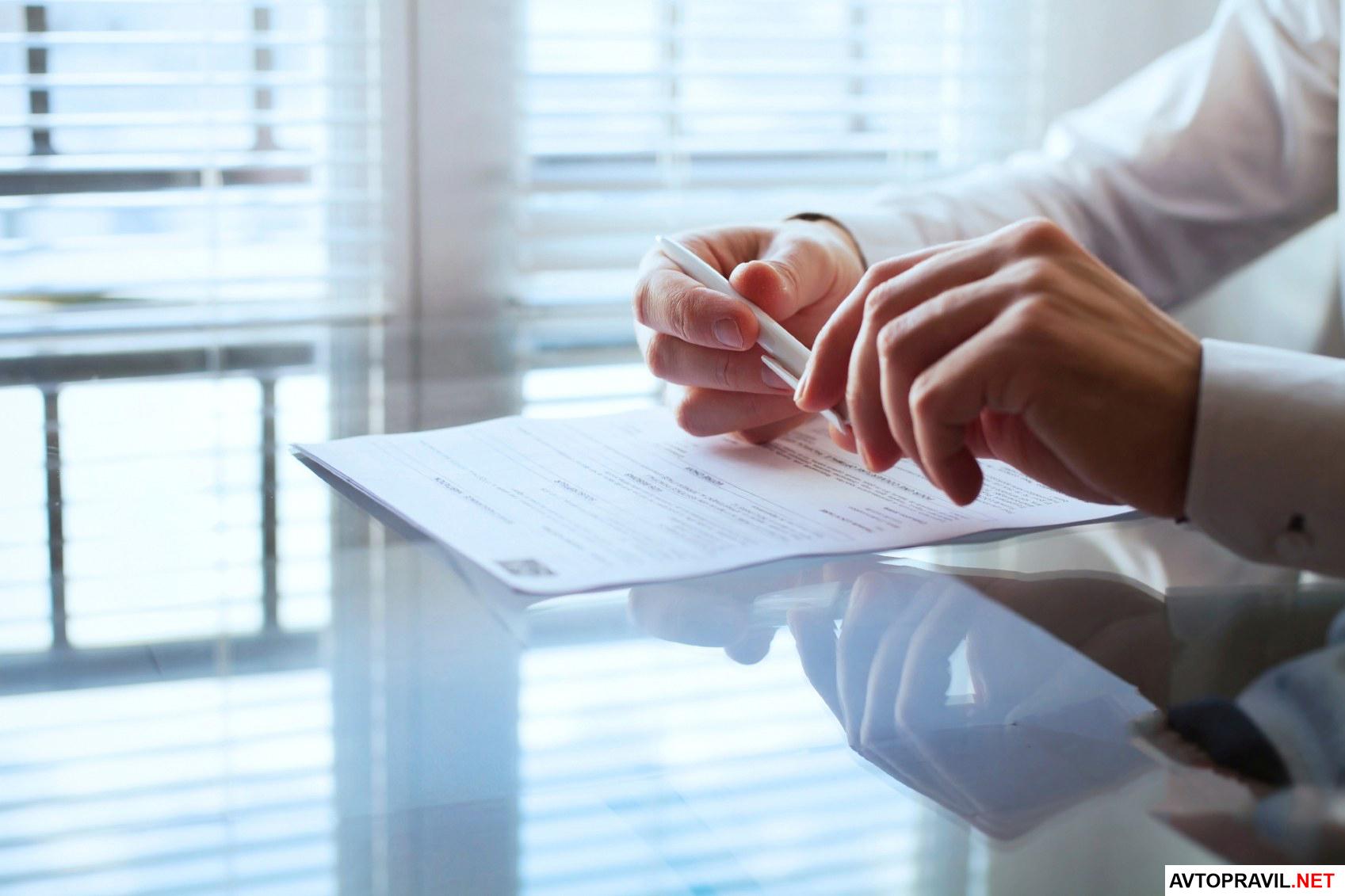 документ на столе, ручка в руках