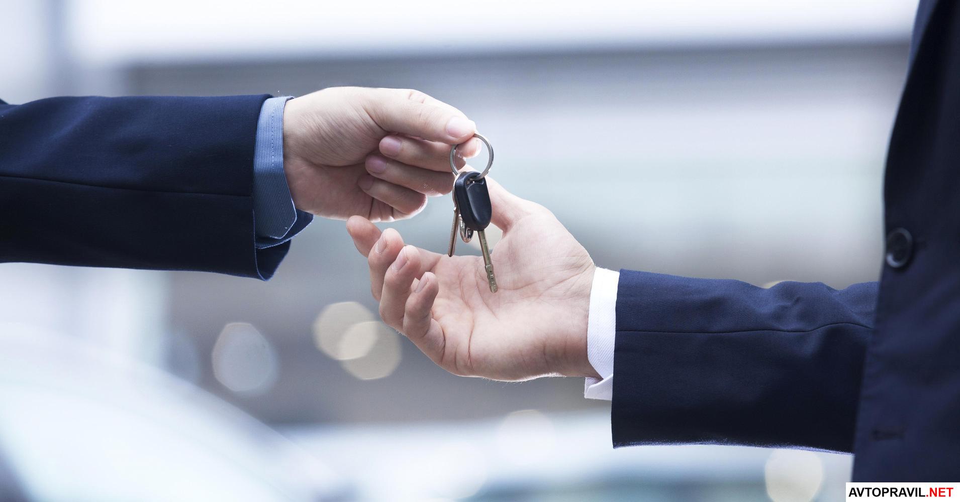 одна рука держит ключи от автомобиля, а вторая их забирает
