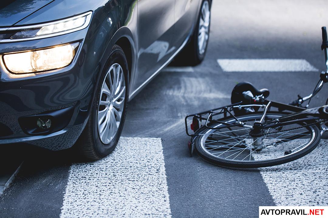 Автомобиль и велосипед, лежащий на дороге