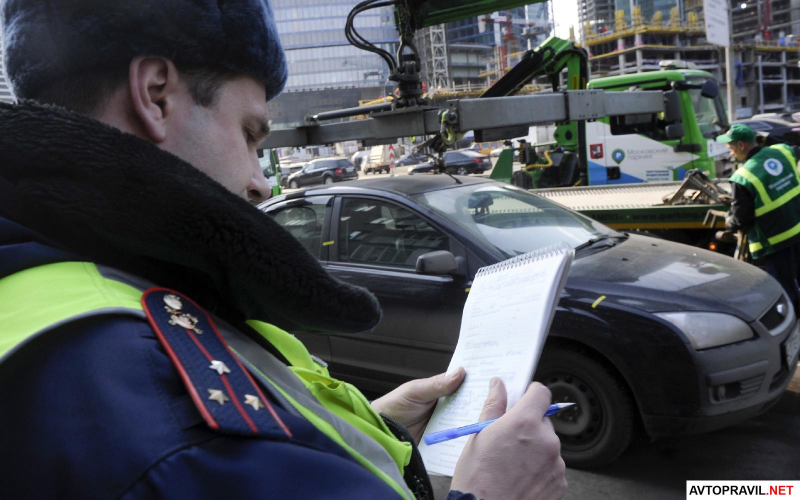 сотрудник гибдд держит блокнонт в руках на фоне эвакуатора, который грузит машину