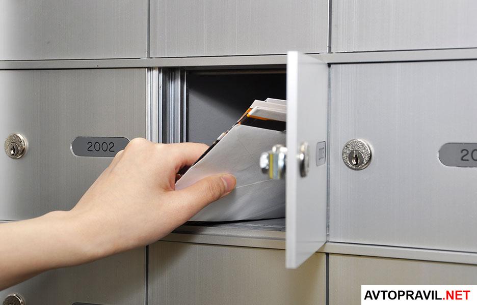рука достает письмо из почтового ящика