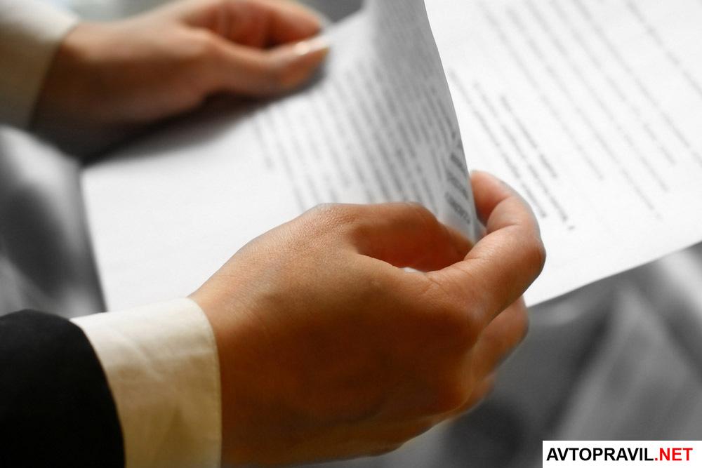 Мужчина держащий в руках документ