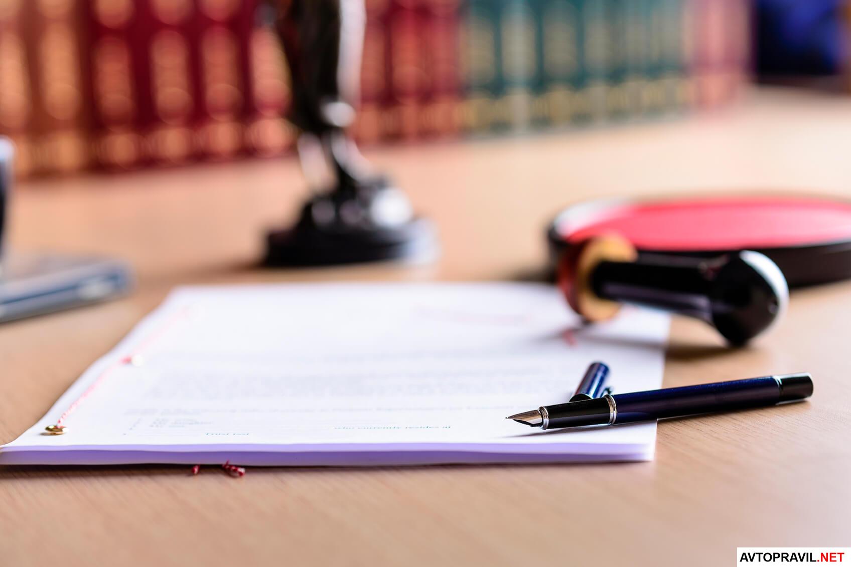 Печать нотариуса и документы с ручкой, лежащие на столе