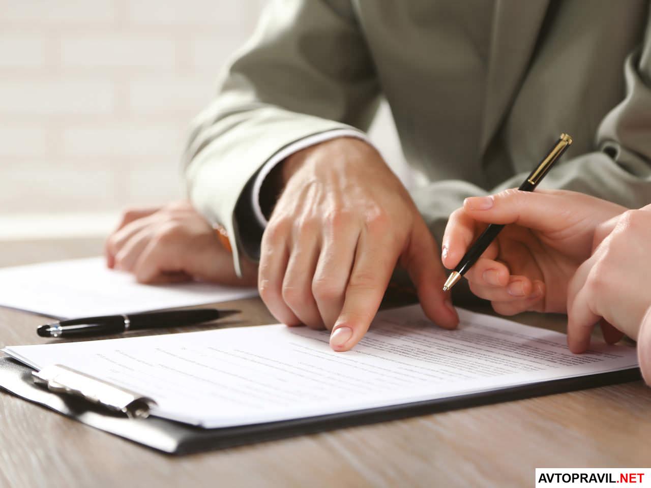 Человек помогающий заполнить заявление другому человеку на листе бумаги