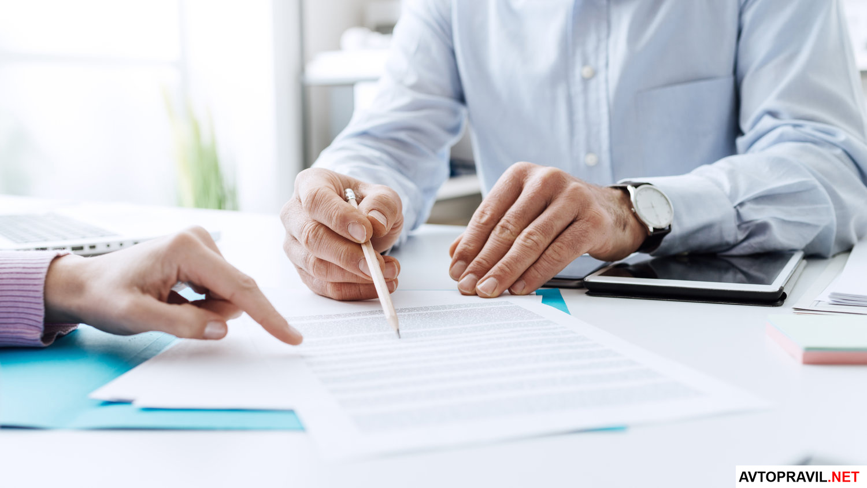 2 человека за столом оформляющие документ