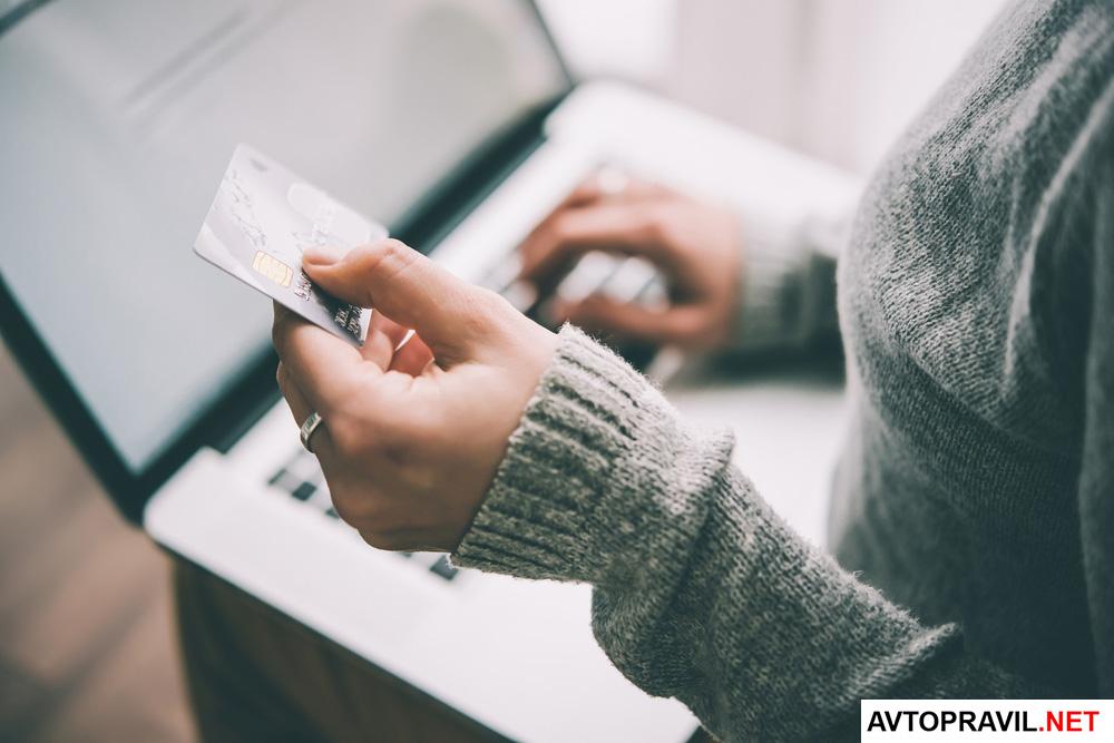 девушка держащая в руках банковскую карту перед компьютером