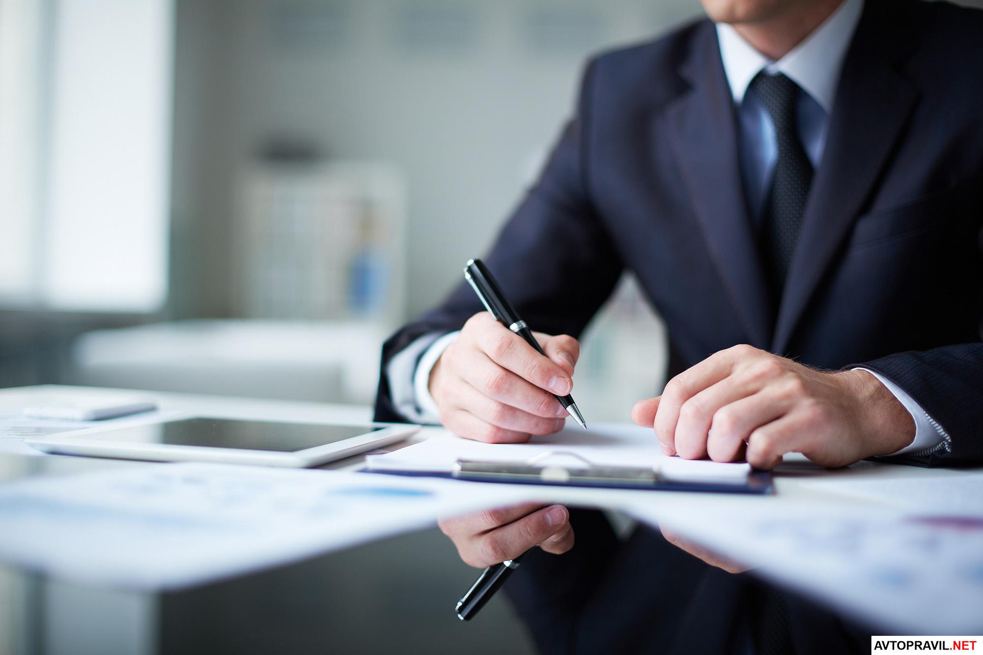 Мужчина пишущий ручкой на бумаге заявление