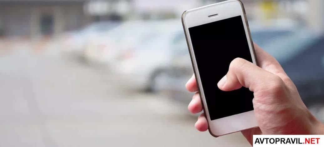 смартфон в руке на фоне дороге