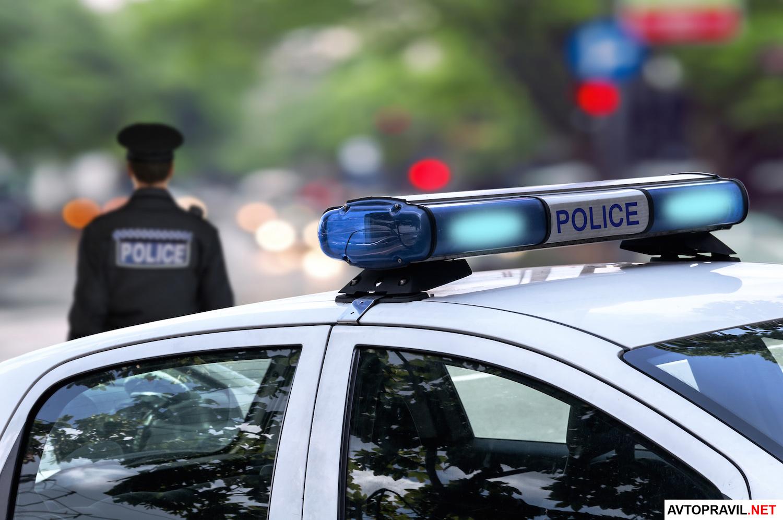 Полицеский стоящий за полицейской машиной