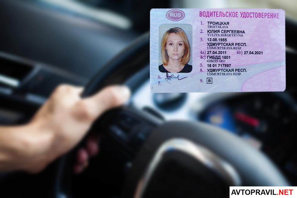 водительское удостоверение на фоне руки держащейся за руль