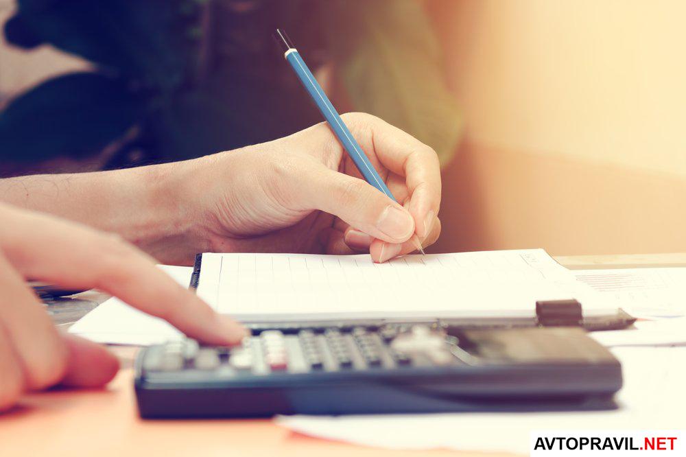 Калькулятор и ручка в руках