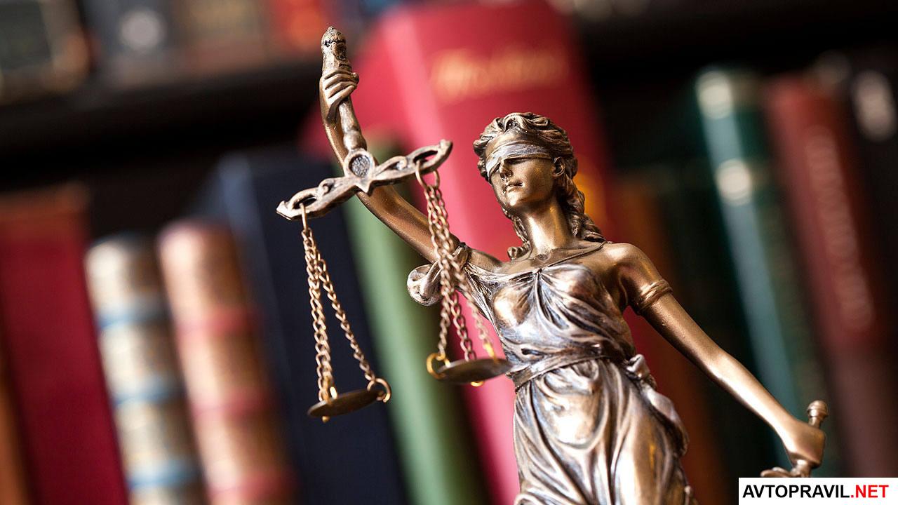 Статуя справедливости на фоне книжек
