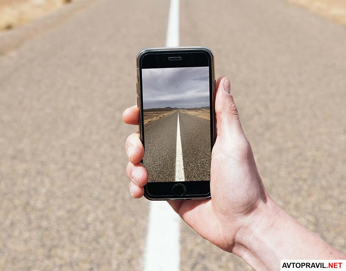 телефон в руках фотографирует разметку на дороге