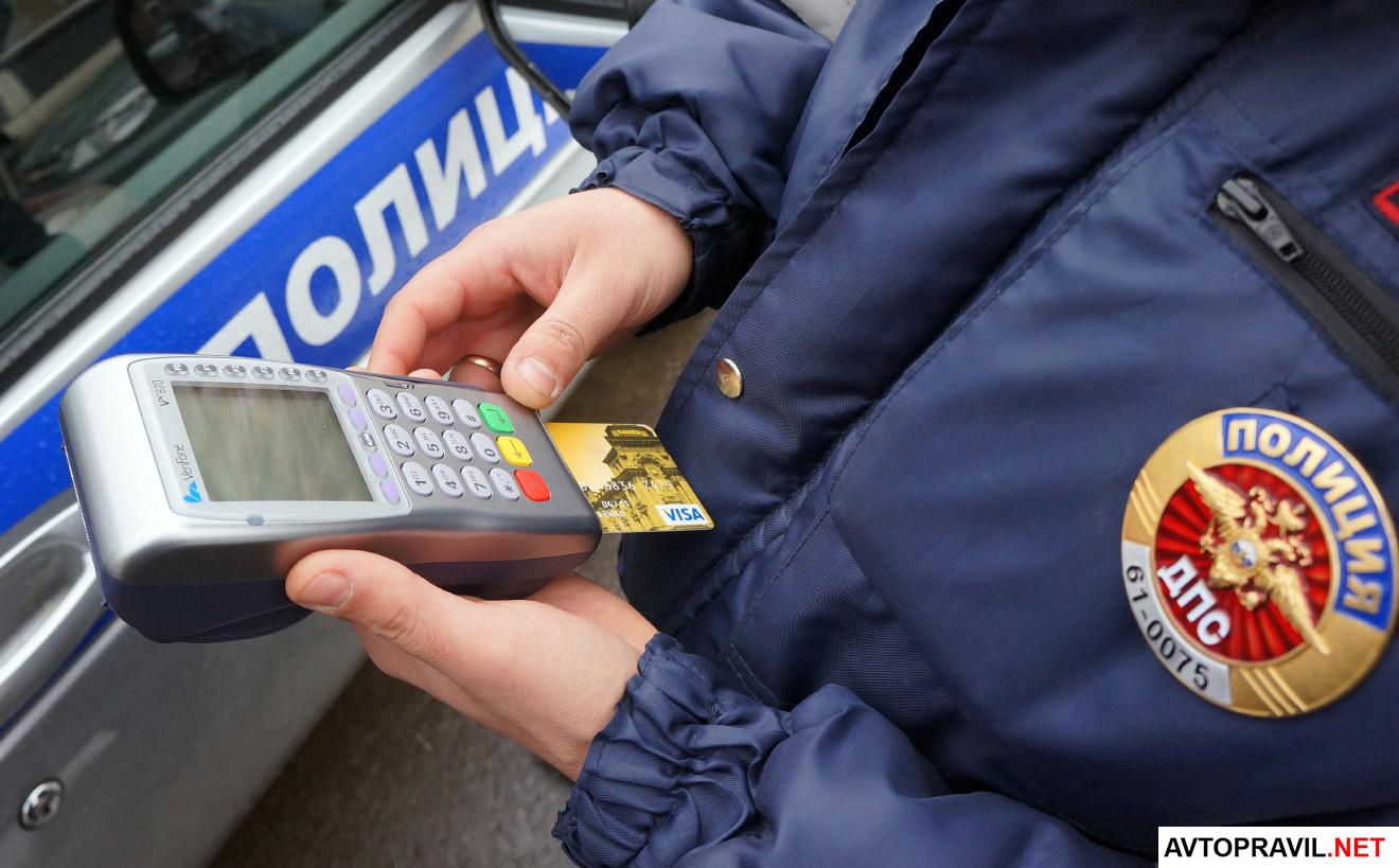 сотрудник полиции держит в руках терминал для оплаты штрафов