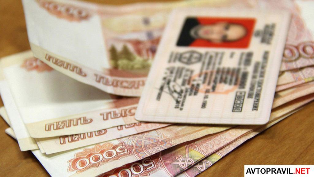 водительское удостоверение, лежащее на деньгах
