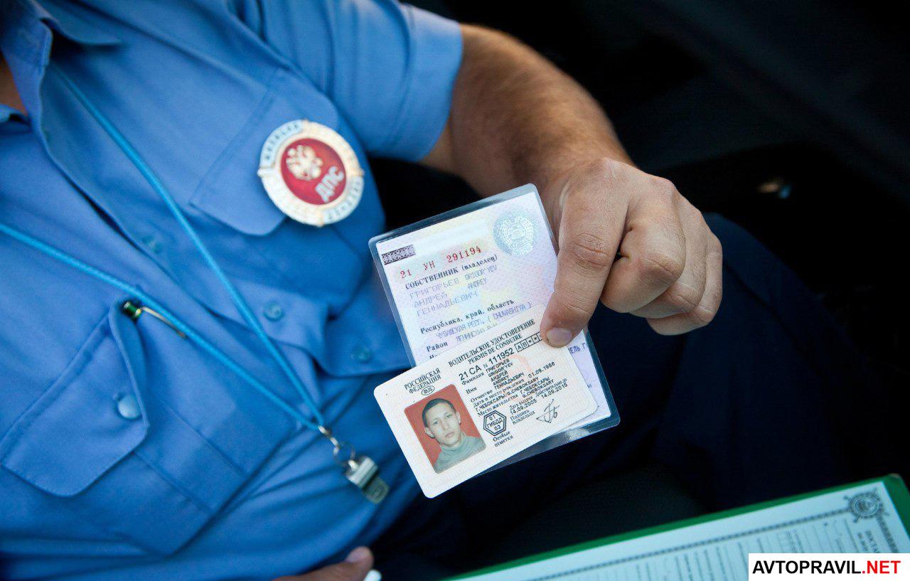 сотрудник гибдд держит в руках водительское удостоверение