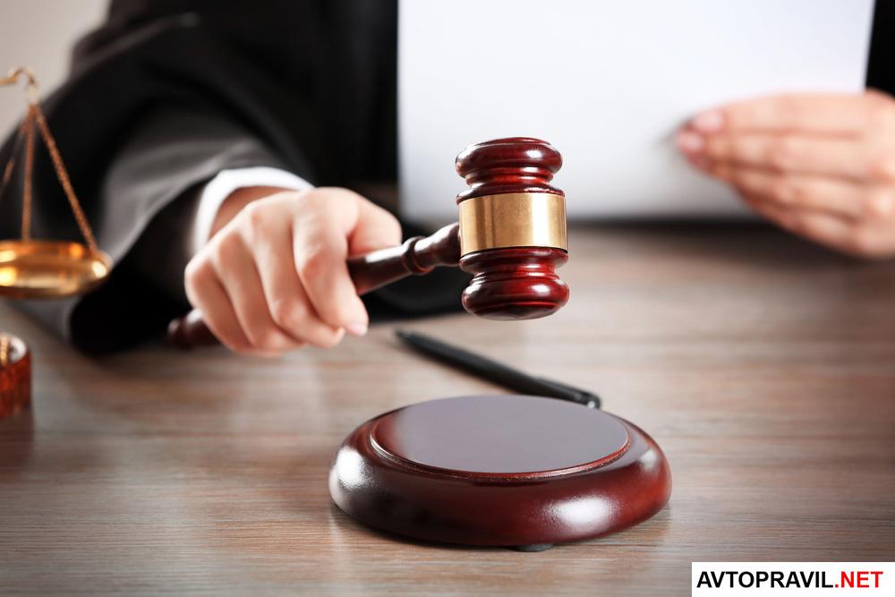 Судья держащий в руках молоток и документ