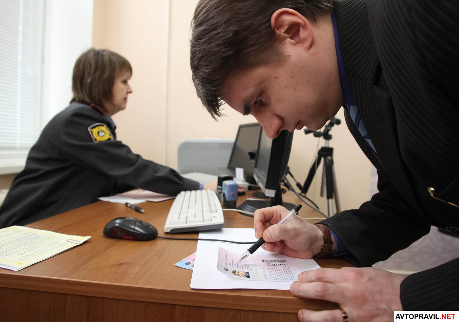 Человек, подписывающий водительское удостоверение в отделении ГИБДД