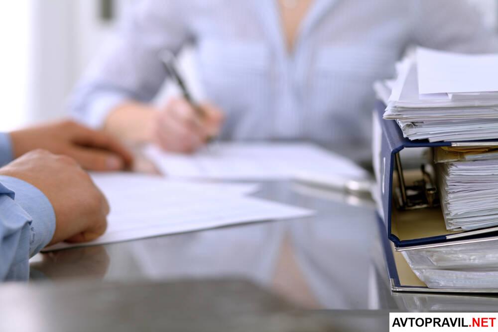 Женщина и мужчина, заполняющие документы