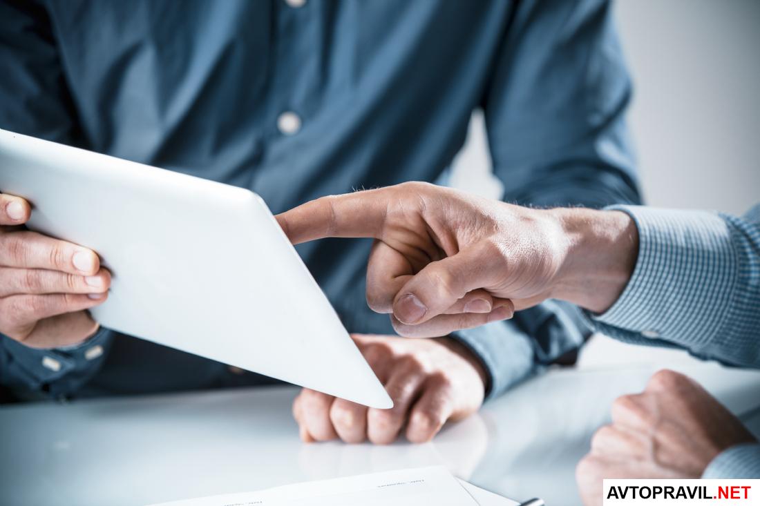 2 человека за столом держат в руках планшет