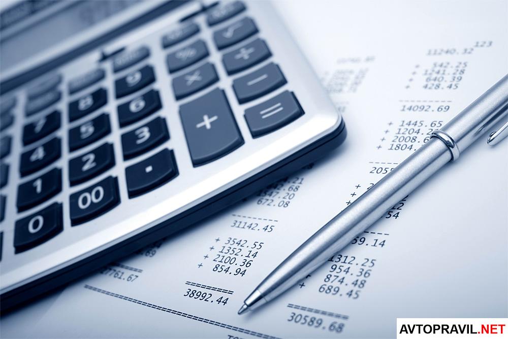 Калькулятор и ручка, лежащие на бумагах расчетами