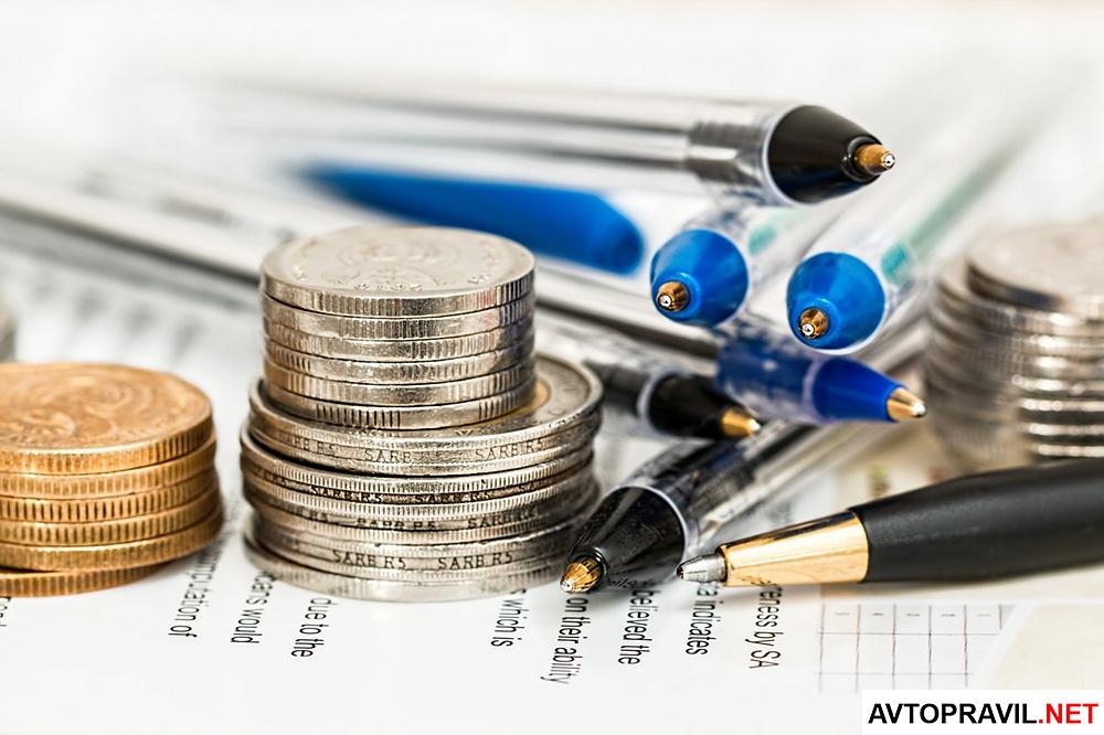 Стопки монет и несколько ручек, лежащие на столе