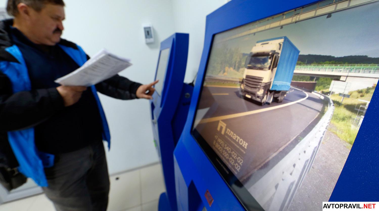 Мужчина оплачивающий транспортный налог в терминале Платон