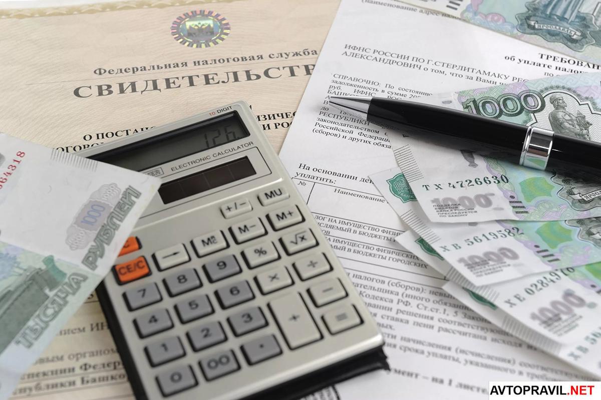 Документы, ручка, деньги и калькулятор лежащие на столе