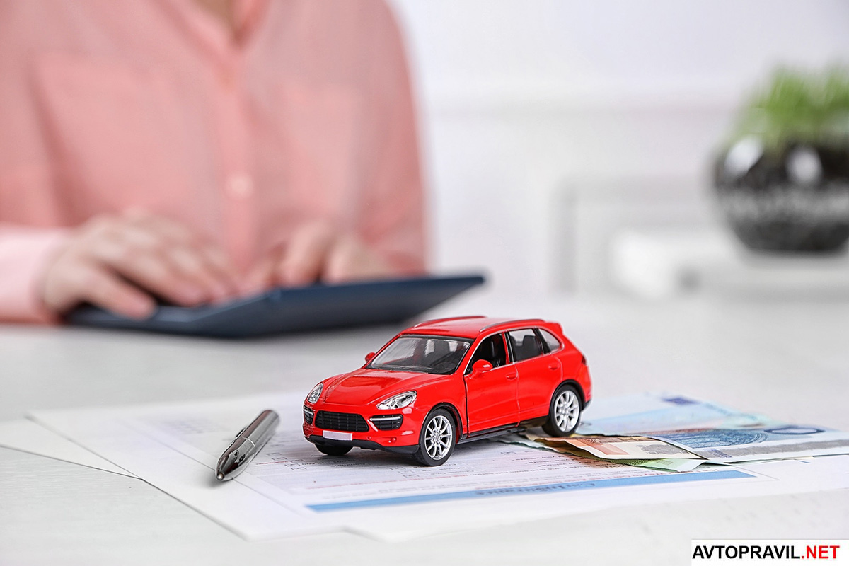 игрушечный автомобиль на бумагах на фоне человека с калькулятором