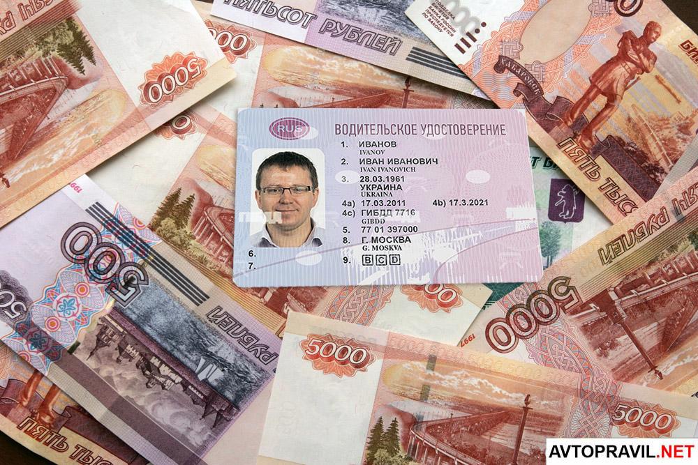 Водительское удостоверение лежащее на рублях