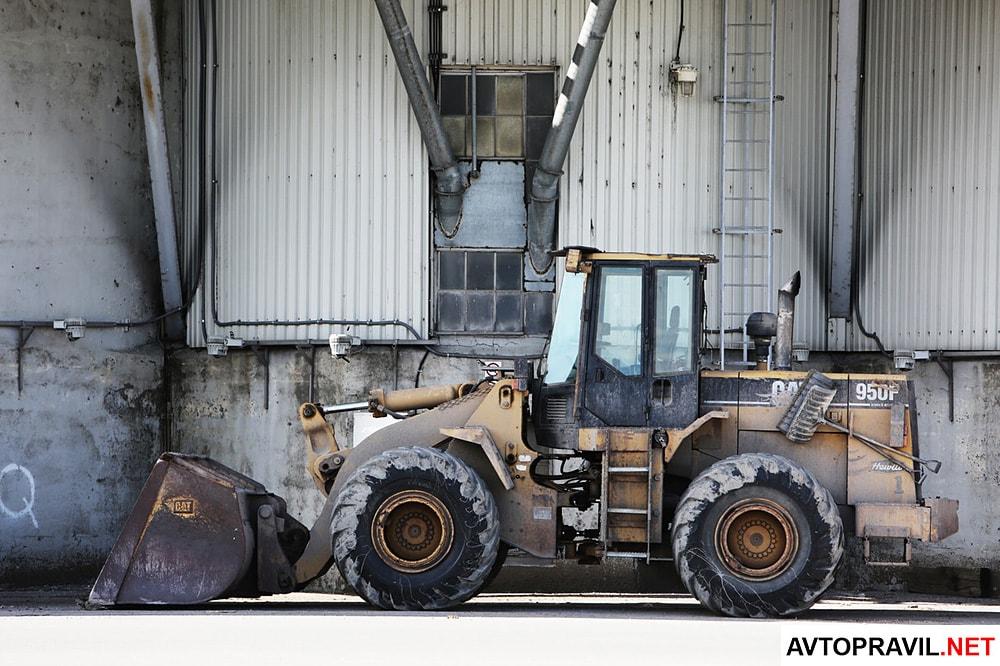 Желтый трактор возле стены