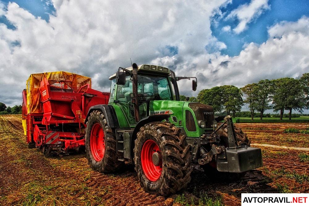 Зеленый трактор едущий по полю