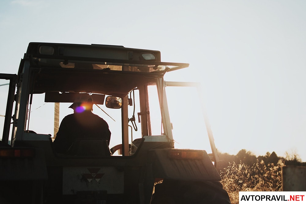 фермер сидит в кабине трактора