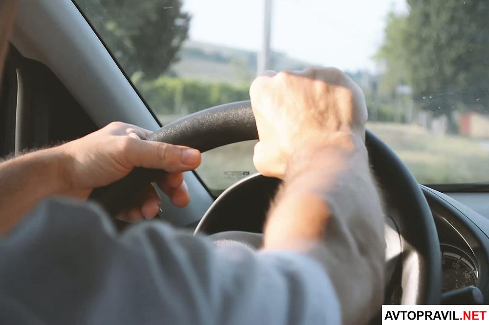 Мужские руки, держащие руль автомобиля