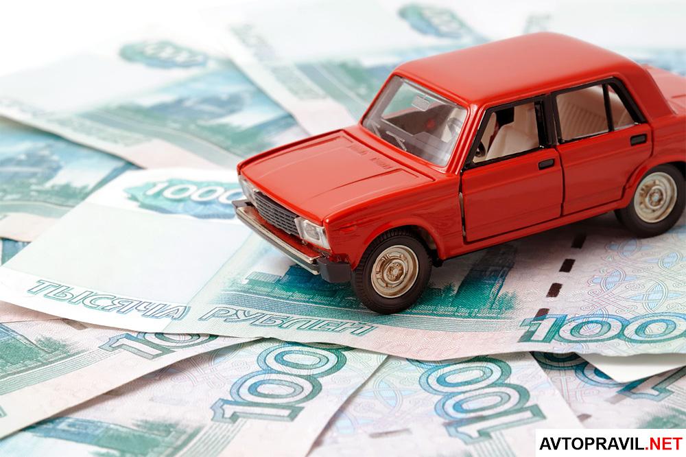 Модель автомобиля и лежащие на столе рубли