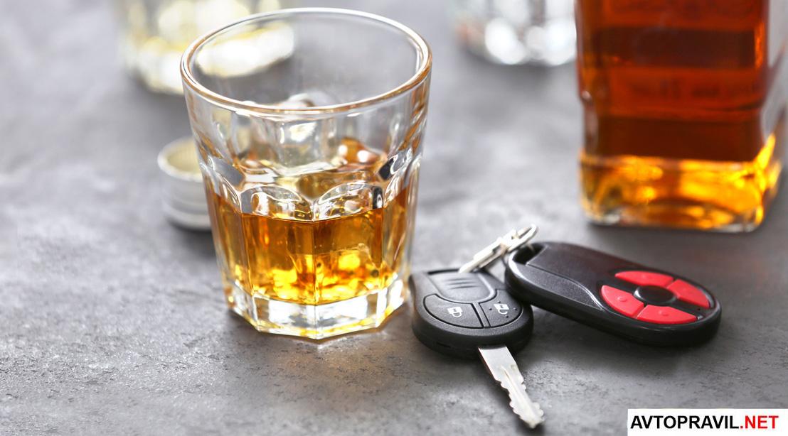 Автомобильные ключи, лежащие на столе и стакан алкогольного напитка