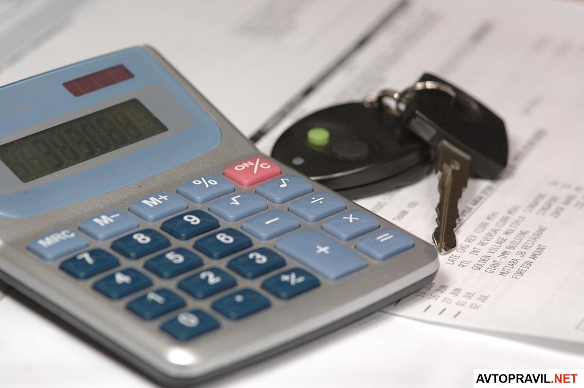 Калькулятор, документ и ключи от авто лежащие на столе