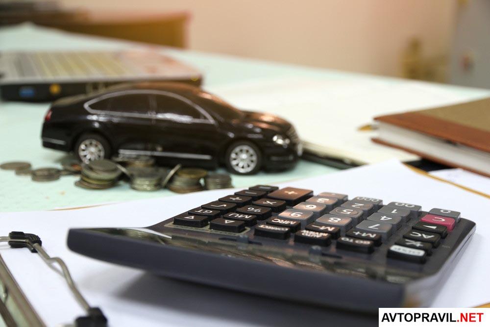 модель авто на столе, а также калькулятор и монеты