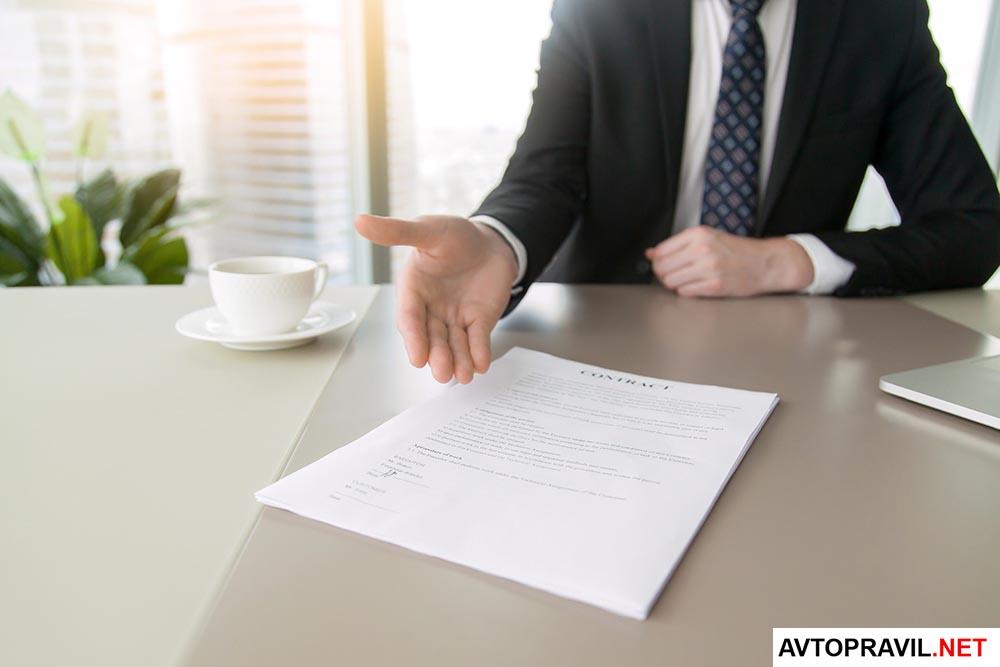 документ на столе и человек с протянутой рукой